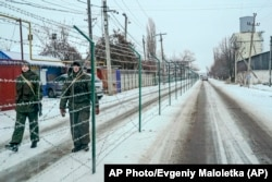 Russian guards patrol an area along the Russian side of the fence in Milove.