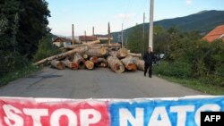 Kosovo -- An ethnic Serb man passes by a barricade set up in the village of Zupce.