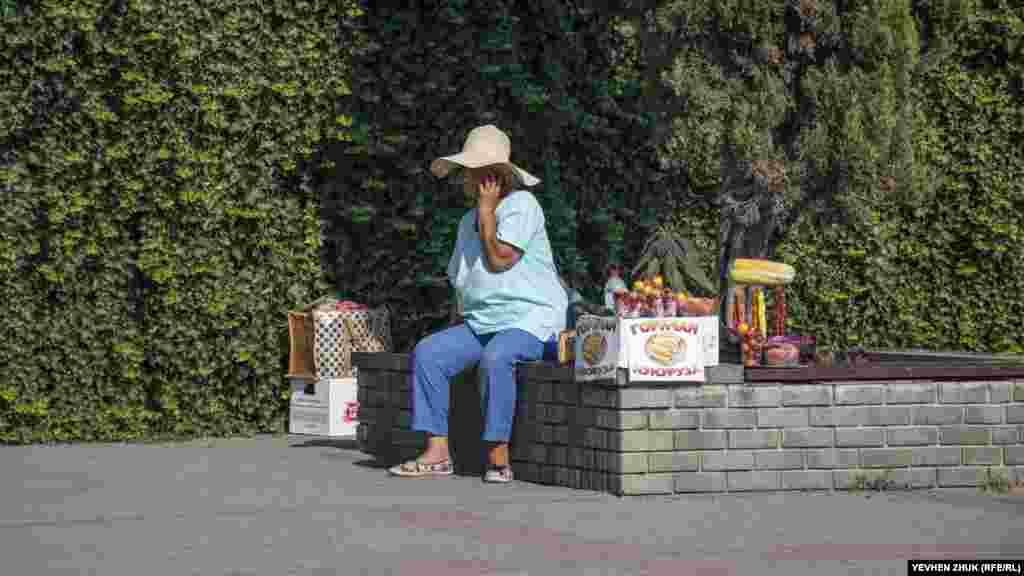 Пожилая женщина торгует алычой, чурчхелой и горячей кукурузой