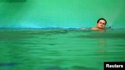 Maria Lenk Aquatics Centreспорт кешеніндегі биіктен секіруге арналған бассейнде түсі жасыл болып өзгерген суда жүзіп жүрген германиялық спортшы Патрик Хаусдинг. Рио, 13 тамыз 2016 жыл.