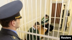 Russian political activists Ivan Gaponov (left) and Artyom Breus sit in a guarded cage during a court hearing in Minsk on March 10.
