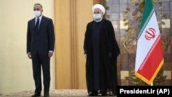 Iranian President Hassan Rohani, right, welcomes Iraqi Prime Minister Mustafa al-Kadhimi as they wear protective face masks to help prevent spread of the coronavirus, during an official arrival ceremony, in Tehran, July 21, 2020