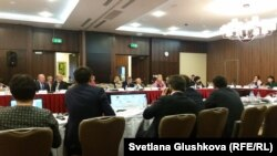 Депутаты парламента и эксперты сидят на конференции о доступе к информации, перед ними установлен экран для презентаций законопроектов. Астана, 25 сентября 2015 года.