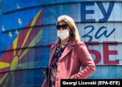 "A woman walks in front of the EU office decorated with Macedonian and EU flags and their logo ""EU for You"" in Skopje."