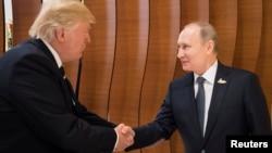 Президенты США и России Дональд Трамп и Владимир Путин пожимают друг другу руки во время саммита G20. Гамбург, 7 июля 2017 года