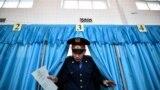 Сотрудник полиции выходит из кабинки для избирателей в день парламентских выборов в Казахстане. Март 2016 года.