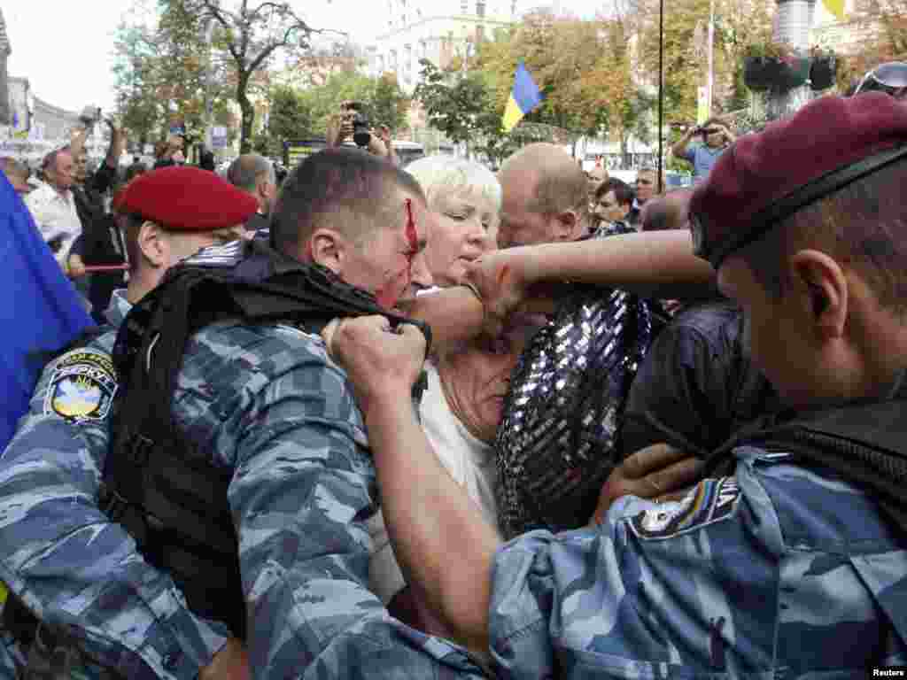 Police officers restrain supporters of former Ukrainian Prime Minister Yulia Tymoshenko outside a court in Kyiv. A Ukrainian court ordered the detention of Tymoshenko following a state prosecutor's motion to take her into custody during her trial on charges of abuse of office.Photo by Vladimir Sindeyev for Reuters