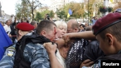 Ukrainian police scuffle amid scuffles as authorities try to restrain supporters of former Ukrainian Prime Minister Yulia Tymoshenko outside the courtroom in Kyiv on August 5, when the judge ordered that Tymoshenko be taken into custody.