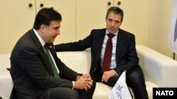 NATO Secretary-General Anders Fogh Rasmussen (right) meets with Georgian President Mikheil Saakashvili, whose party lost the recent elections, during the plenary session of a NATO Parliamentary Assembly in Prague on November 12.