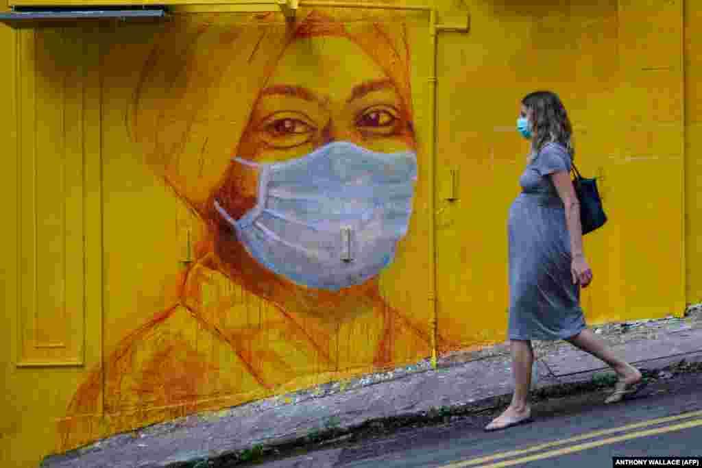 Девушка в защитной маске и граффити в Гонконге.