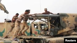 Iraqi soldiers load a projectile into a multiple rocket launcher east of Mosul on October 24.