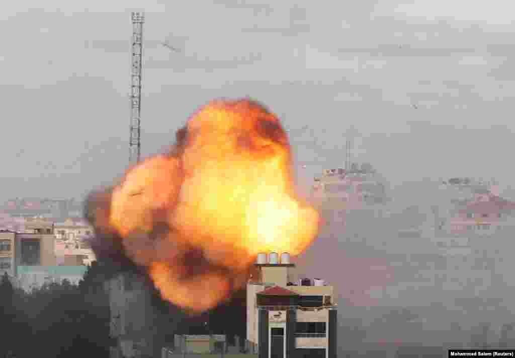 Видно дим і полум'я після авіаудару Ізраїлю по будівлі в місті Газі 18 травня 2021 року. Нинішнє збройне загострення ризикує спровокувати гуманітарну катастрофу: за даними ООН, понад 38 тисяч палестинців були переміщені в Газі, а ще 2500 втратили свої будинки