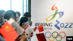 Пекинде 2022 жылғы 26-қысқы олимпиада ойындарын өткізу баннері қасында тұрған адамдар. (Көрнекі сурет).