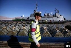 یک سرباز اسرائیلی در حال عبور از مقابل تسلیحات پیاده شده از کشتی باری پانامایی در مارس ۲۰۱۴ در بندر ایلات