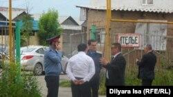 Представители местных властей и сотрудники полиции у ворот объекта в Шымкенте.