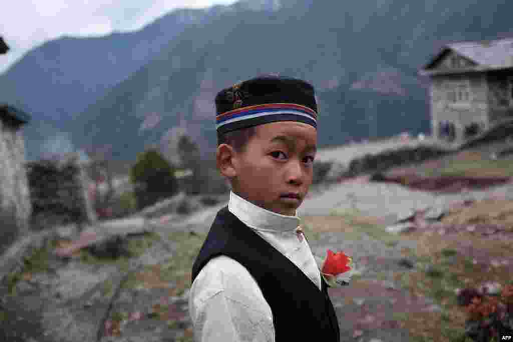 Rinji, 10, a young resident of the northeastern Nepalese town of Lukla, wears a plastic flower on his lapel near his school. (AFP/Roberto Schmidt)