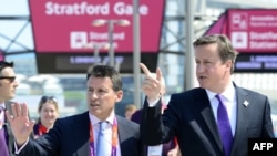 British Prime Minister David Cameron (right) speaks to London Olympics organizer Sebastian Coe during a visit to the Olympic Park in London on July 26.