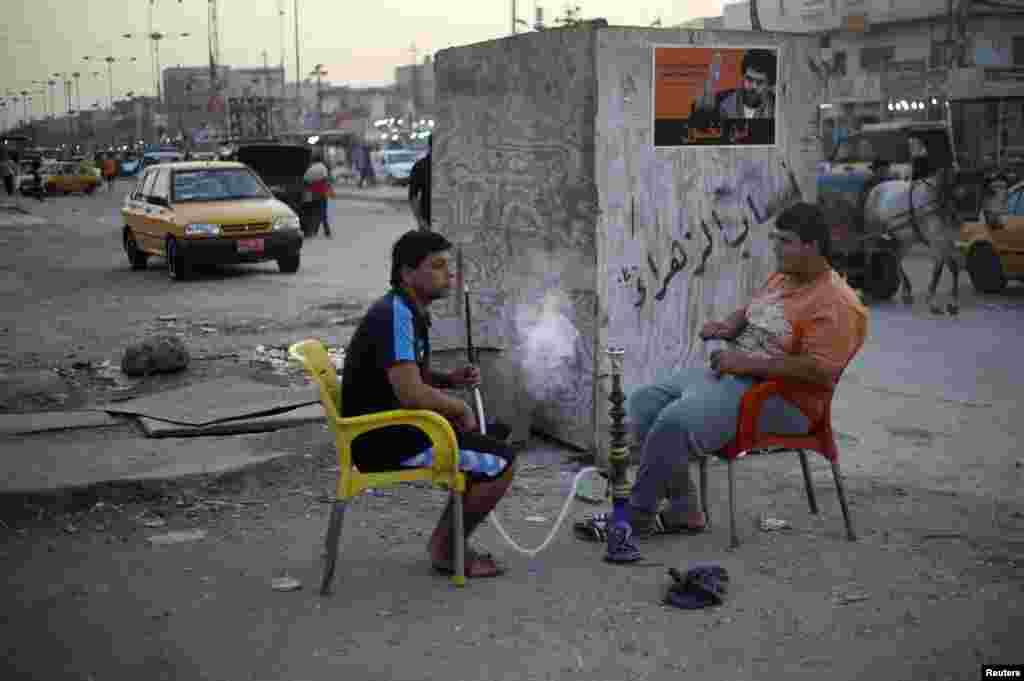 Young men smoke water pipes in Sadr City.