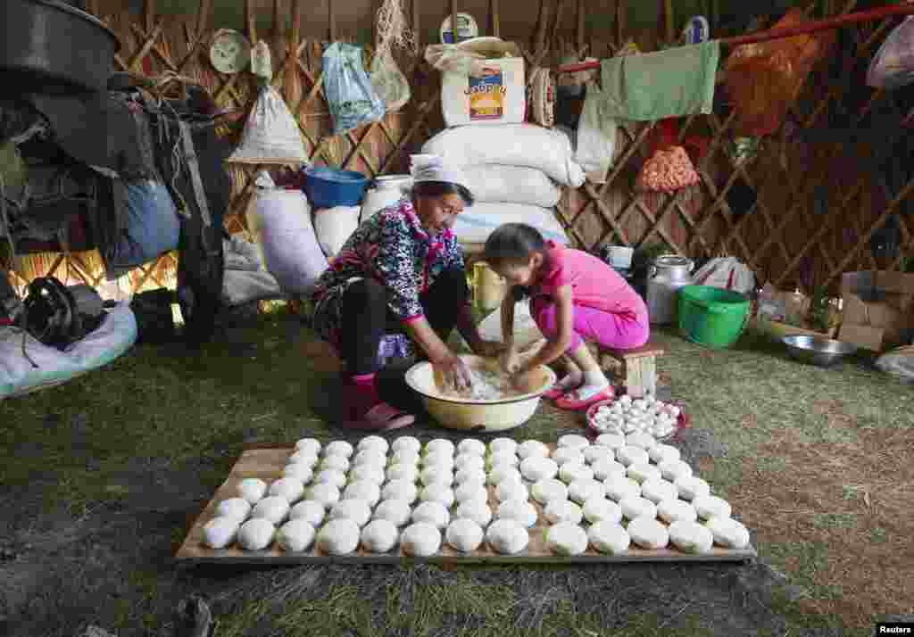 Zhambytai Zhumaliyava and her granddaughter Ayazhan prepare traditional cheese curd balls, which are left out to dry.