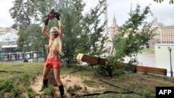 Активистка женского движения FEMEN Инна Шевченко спилила православный крест. Киев, 17 августа 2012 года.