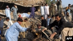 Pakistani volunteers and local residents search for blast victims in the rubble following the suicide car-bomb blast on the outskirts of Peshawar on November 16.