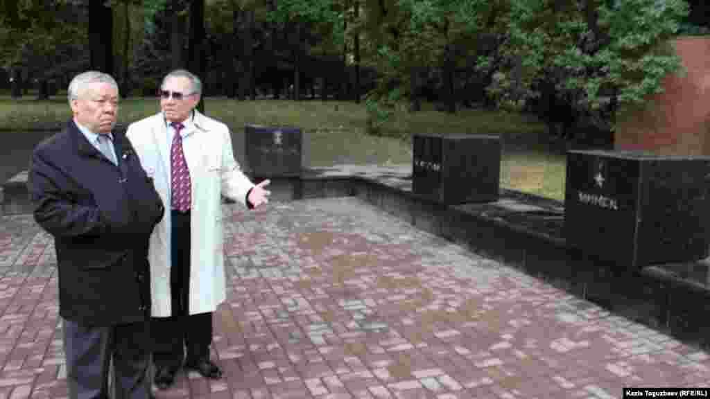 Депутат парламента генерал-лейтенант Бахытжан Ертаев (слева) осматривает поврежденные тумбы, посвященные городам-героям бывшего Советского Союза.