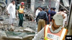 Rescue worker inspects the scene of the attack at the Sufi shrine