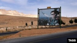 A billboard depicting Syrian President Bashar al-Assad is seen on a road from Damascus to Homs.