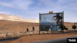 Білборд з выявай прэзыдэнта Сырыі Башара аль-Асада на дарозе з Дамаска ў Хомс. 13 кастрычніка 2015 году