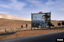 Дамаск шаарынын Хомско кеткен жолдун боюндагы Башар Асаддын сүрөтү тартылган билборд. 13-октябрь, 2015