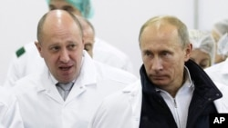 Businessman Yevgeny Prigozhin (left) shows Russian President Vladimir Putin around a St. Petersburg factory of his that produces school lunches.