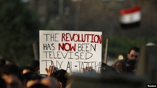 Egyptian antigovernment protesters carry a sign outside the Egyptian television center in Cairo during demonstrations that toppled the Mubarak regime in February 2011.