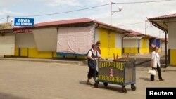Люди проходят по прилегающей к рынку территории. Минск, 23 июня 2013 года.
