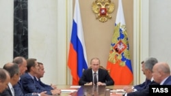 Russian President Vladimir Putin chairs a meeting with members of the Security Council to discuss additional security measures for Crimea on August 11.