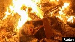 Портрет президента Украины Виктора Януковича, брошенный в костер возле разгромленного здания Службы безопасности во Львове, Украина. 19.02.2014