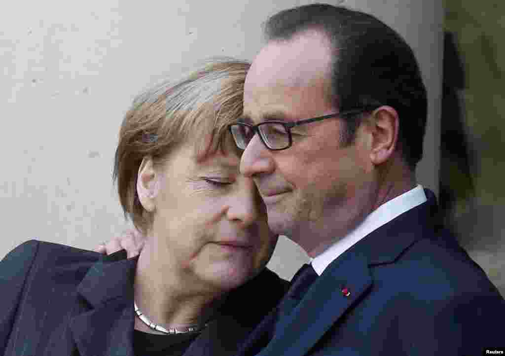 French President Francois Hollande welcomes German Chancellor Angela Merkel at the Elysee Palace before the march.