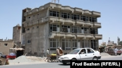 An apartment building stands unfinished on a street in Kabul