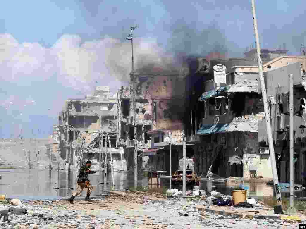 Liviyada Sirte şəhərini tutmaq istəyən Milli Keçid Hökumətinin döyüşçülərindən biri snayperdən qorunmaq üçün qaçır. 14 oktyabr. (Foto:Mohamed Messara)