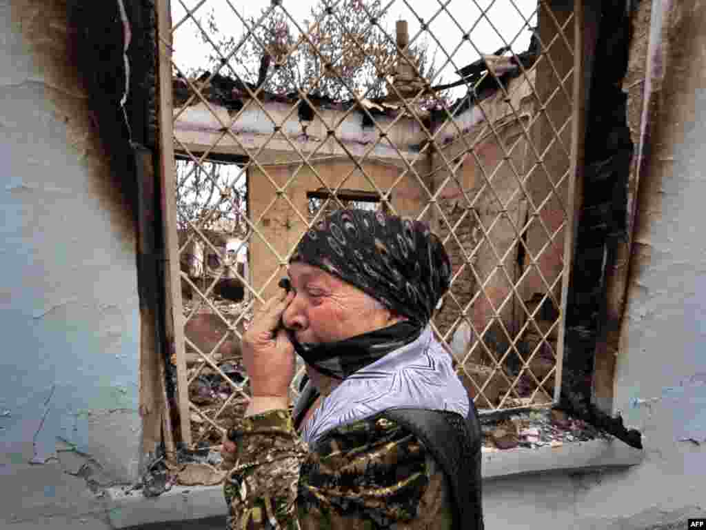 Kyrgyzstan -- An ethnic Uzbek woman cries as she passes by a burnt-out house in the town of Osh, 24Jun2010 - KYRGYZSTAN, Osh : An ethnic Uzbek woman cries as she passes by a burnt-out house in the town of Osh on June 24, 2010. Almost all the refugees who fled Kyrgyzstan during ethnic clashes and crossed the border into Uzbekistan have now returned, the deputy head of the country's border service said.