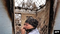An ethnic Uzbek woman cries as she passes by a burned-out house in the town of Osh on June 24.