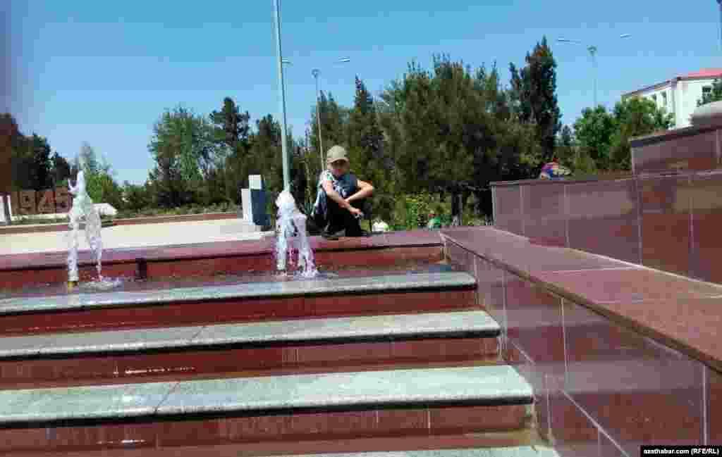 Mary welaýatynda fontanyň gyrasynda oturan oglanjyk. Türkmenistanda adamlaryň yssy howadan