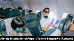 Пассажиры в салоне самолета в аэропорту Алматы.