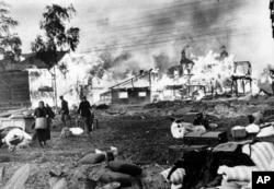 Мужчины и женщины спасают свои пожитки из горящих домов, подожжённых советскими солдатами в рамках политики выжженной земли, пригород Ленинграда, 21 октября 1941 года