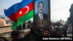 Mourners carry an Azerbaijani flag and a portrait of Zaur Ahmadov, who died four days after he lit himself on fire in Baku to protest perceived mistreatment.
