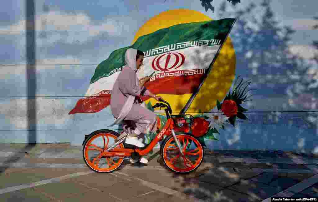 Іранская жанчына на ровары ў Тэгеране на тле графіці з нацыянальным сьцягам Ірану.