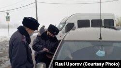 Полицейские вручают сидящему в машине журналисту Лукпану Ахмедьярову повестку. Западно-Казахстанская область, 3 февраля 2021 года.