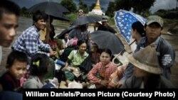 Безгек менен ооруган баланы бейтапканага алып бараткан Мьянманын жашоочулары.