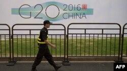 G20 саммиті өтетін Ханчжоу қаласында қонақүй жанынан өтіп бара жатқан қауіпсіздік қызметкері. Қытай, 2 қыркүйек 2016 жыл.
