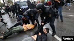 Поліція повалила на землю чоловіків біля однієї з виборчих дільниць у місті Сан-Жульян-де-Раміс у іспанському регіоні Каталонія, де регіональна влада оголосила референдум щодо незалежності, 1 жовтня 2017 року