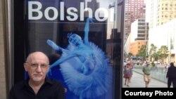 Соломон Волков на фоне афиши Большого театра в Нью-Йорке, 2014 год